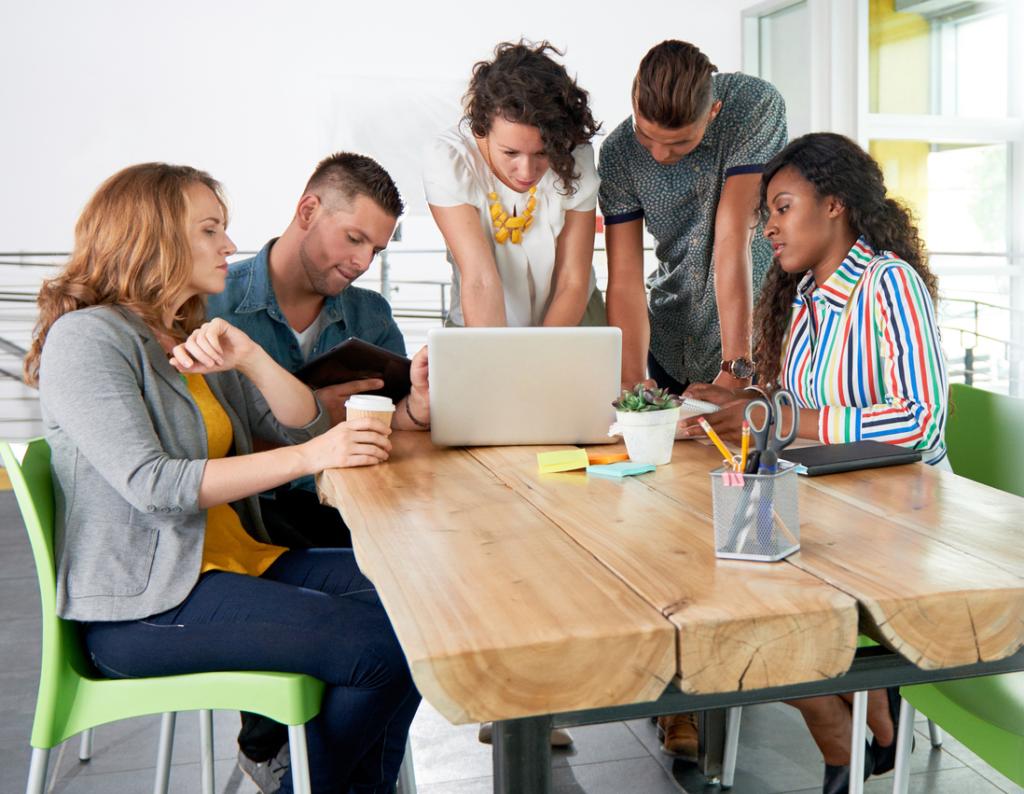 Millennial group around laptop