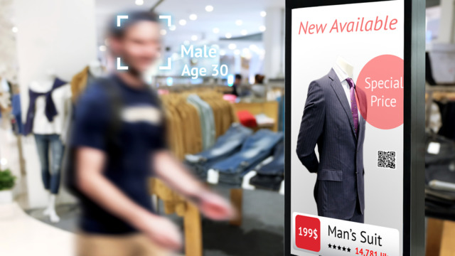 male in retail store next to printed sign